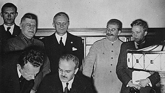 The pact was signed by Molotov (seated) and Ribbentrop (standing 3rd from left)